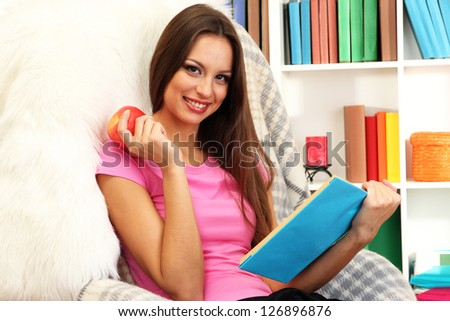Portrait of female eating apple and reading book at home