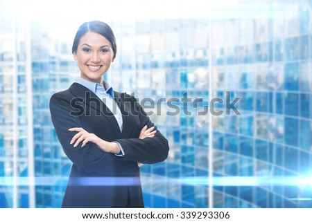Portrait of female executive with hands crossed, blue background. Concept of leadership and success - stock photo