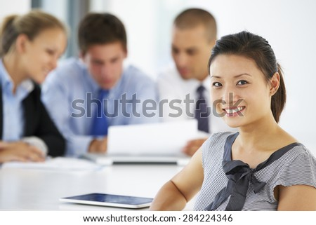 Portrait Of Female Executive With Office Meeting In Background