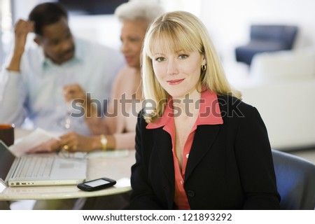 Portrait of female financial adviser smiling while senior couple sitting in background