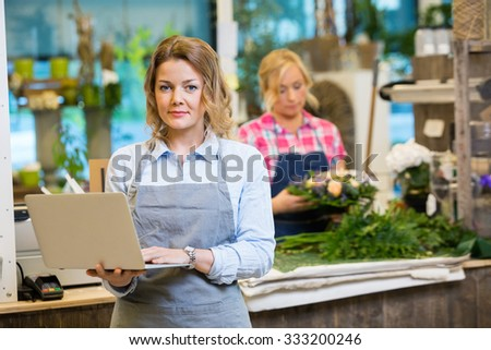 Portrait of female florist using laptop with colleague working in background at flower shop - stock photo