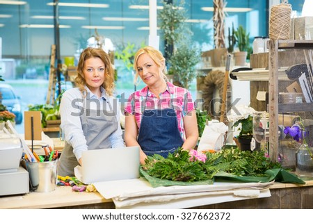 Portrait of female florists with laptop on counter in flower shop - stock photo