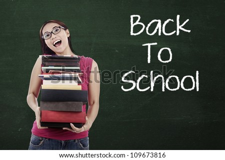 Portrait of female high school student holding pile of textbooks with text of Back To School on the blackboard - stock photo