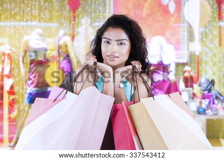 Portrait of female indian model carrying shopping bags at the shopping center - stock photo