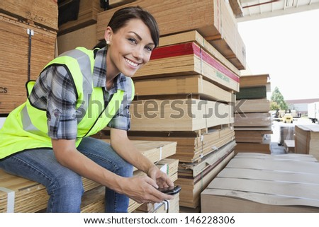Portrait of female industrial worker using cell phone while sitting on stack of wooden planks - stock photo