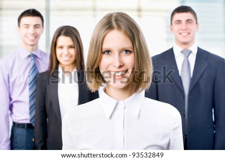Portrait of female leader with cheerful team in background