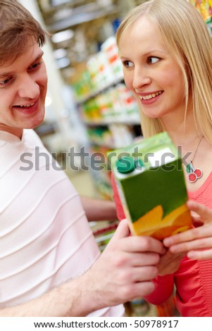 Portrait of female looking at smiling man in supermarket while choosing juice