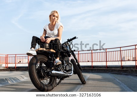 Portrait of female model Biker sitting on vintage custom motorcycle. Outdoor lifestyle portrait - stock photo