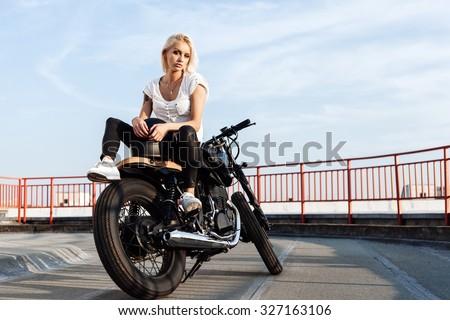 Portrait of female model Biker sitting on vintage custom motorcycle. Outdoor lifestyle portrait - stock photo