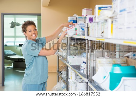 Portrait of female nurse smiling while working in storage room of cancer hospital - stock photo