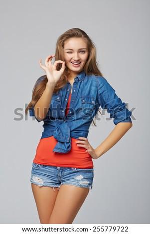 Portrait of female okay gesturing, on gray background - stock photo