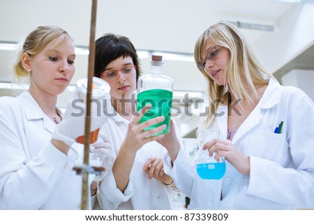 portrait of female researchers/chemistry students carrying out research in a chemistry lab (color toned image; shallow DOF) - stock photo