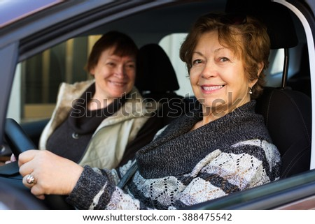Portrait of female senior driver and her friend in car - stock photo