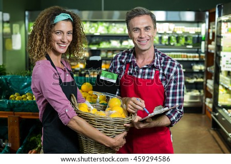 Portrait of female staff holding basket of fruits and male staff with clipboard in supermarket
