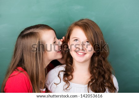 Portrait of female student telling a secret to her friend in a close up portrait - stock photo