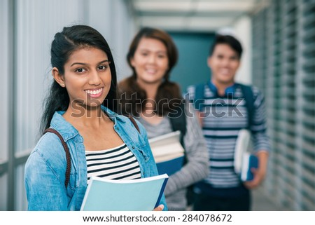 Portrait of female student with her friends in the background - stock photo