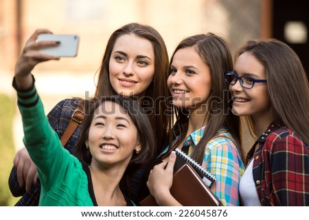Portrait of female students that are making pictures with university building in the background. - stock photo