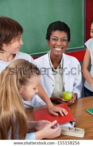 Portrait of female teacher holding apple with students standing at desk in classroom - stock photo