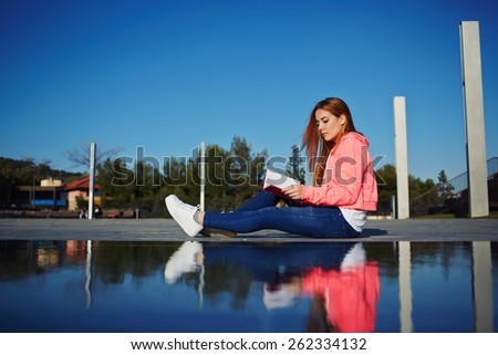 Portrait of female teenager reading absorbing book and eat green apple while sitting in the park, attractive young woman relaxing on her holiday while read literature outdoors, student on the campus - stock photo