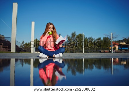 Portrait of female teenager reading absorbing book and eat green apple while sitting in the park, attractive young woman enjoy her holiday while read literature outdoors, student on the campus - stock photo