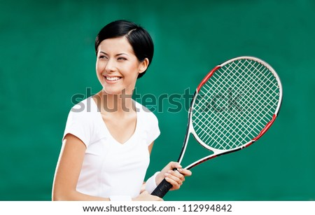 Portrait of female tennis player with racquet at the tennis court - stock photo