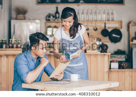 portrait of female waitress explain about the menu to her cutomer - stock photo
