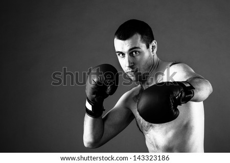 portrait of fighter in boxing pose on gray background