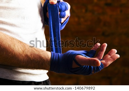 portrait of fighteris applying bondage tape on hands - stock photo