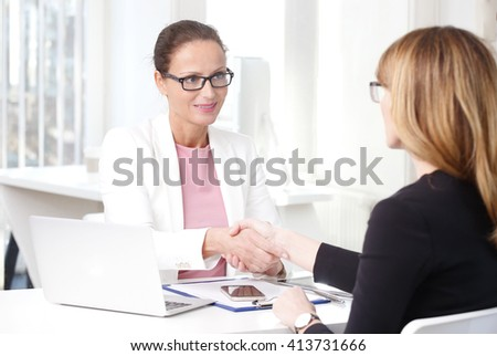 Portrait of financial advisor woman shaking hands with businesswoman while sitting at desk in front of laptop. - stock photo