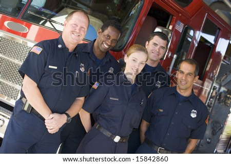 Portrait of firefighters standing by a fire engine - stock photo