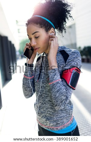 Portrait of fit and sporty young woman listening to music with mobile phone.