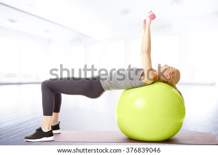 Portrait of fit woman exercising on a fitness ball and using weight.