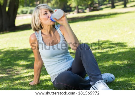 Portrait of fit woman sitting on grass while drinking water in the park - stock photo