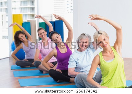 Portrait of fit women practicing stretching exercise in gym class - stock photo