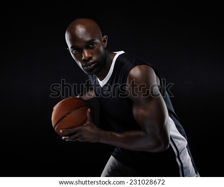 Portrait of fit young male athlete playing basketball. African american basketball player against black background - stock photo