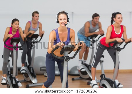 Portrait of fit young people working out at class in gym - stock photo