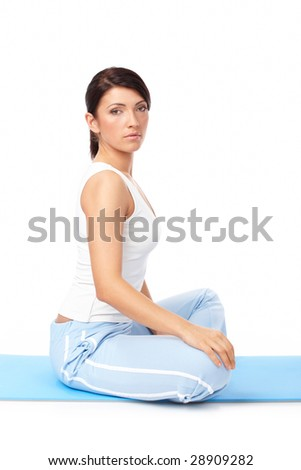 Portrait of fit young woman sitting on mat, isolated on white - stock photo