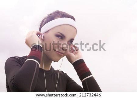 Portrait of Fitness Caucasian Woman Listening to Music during Her Training Outdoors. Horizontal Image Composition - stock photo