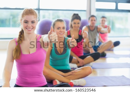 Portrait of fitness class and instructor gesturing thumbs up on yoga mats