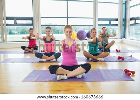 Portrait of fitness class and instructor gesturing thumbs up on yoga mats - stock photo