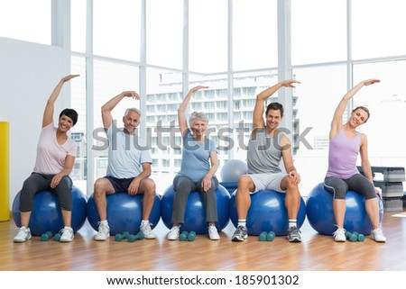 Portrait of fitness class sitting on exercise balls and stretching hands in a bright gym
