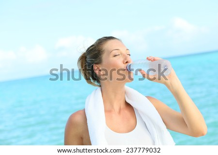 Portrait of fitness woman drinking water after working out - stock photo