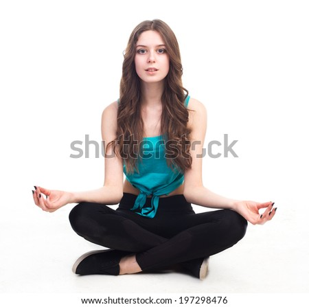 Portrait of fitness young woman sitting cross-legged in lotus position over white background - stock photo