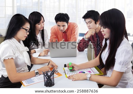 Portrait of five businesspeople sitting in the meeting room and discussing financial report - stock photo