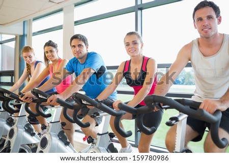 Portrait of five people working out at a stationary bicycle class in the gym