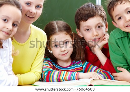 Portrait of five pupils looking at camera with open book near by - stock photo