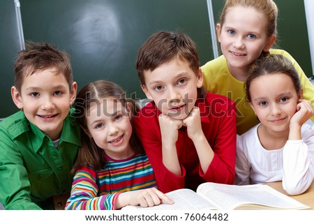 Portrait of five pupils sitting in classroom with open book near by - stock photo