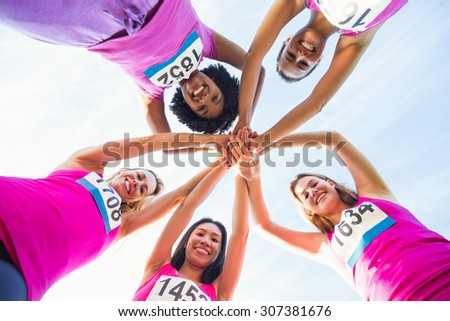 Portrait of five smiling runners supporting breast cancer marathon in parkland - stock photo