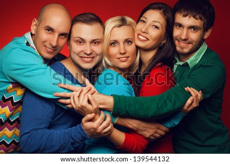Portrait of five stylish close friends hugging, smiling and posing over red background. Guys having fun. Hipster style. Studio shot - stock photo