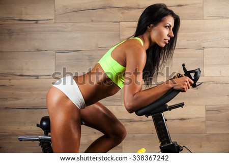 Portrait of focused young woman wearing sport bra and using a exercise bike at the gym - stock photo